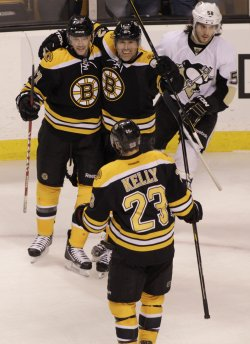 Bruins Pouliot congratulated by teammates after scoring against Penguins at TD Garden in Boston, MA.