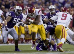 USC Trojans' tight end Xavier Grimble bulls his way first down before being tackled by Washington Huskies linebacker Thomas Tutogi in Seattle.