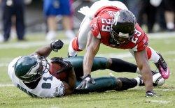 Atlanta Falcons Brian Williams dives over Philadelphia receiver Jason Avont.