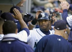 Seattle Mariners' Ken Griffey Jr. is greeted in the dugout after hitting a three run RBI homer.