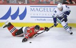 Blackhawks Frolik and Canucks Samuelsson go for puck in Chicago