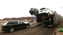 Range Rovers are loaded onto a transport truck in the port city of Tianjin in China