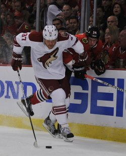Phoenix Coyotes Raffi Torres and Chicago Blackhawks Dylan Olsen fight for the puck in Chicago