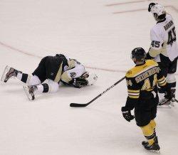 Penguins Dupuis falls on Bruins Seidenberg at TD Garden in Boston, MA.