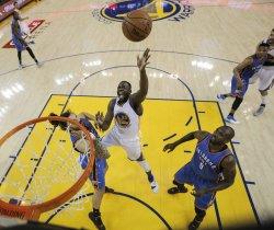 Warriors' Draymond Green shoots over Thunder's Steven Adams