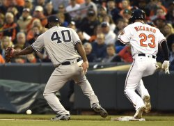 Orioles' Joey Rickard is safe at first base after the fielding error by Yankees pitcher Luis Severino