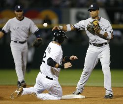 Chicago White Sox's A.J. Pierzynski slides into second base as New York Yankees second baseman Robinson Cano throws to first base to try for a double play