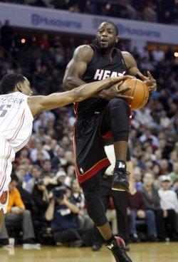 Miami Heat guard Dwyane Wade shoots over Charlotte Bobcats guard Gerald Henderson