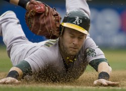 Oakland Athletics' Daric Barton barely makes it back to first base while being tagged by Seattle Mariners' Casey Kotchman