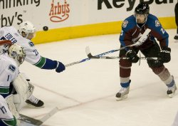 Avalanche Hejduk Battles for Puck Against Canucks Edler in Denver