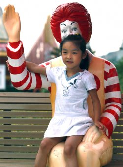 A Chinese girl sits on the lap of the iconic Ronald McDonald in Qingdao