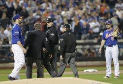 New York Mets Matt Harvey stands near 3 umpires