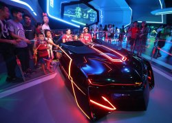 Chinese pose for photos in the Tron exhibition hall in Shanghai Disneyland, China