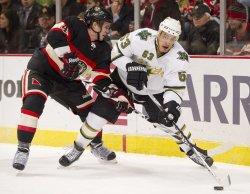 Stars Ribeiro looks to pass as Blackhawks Hjalmarsson defends in Chicago