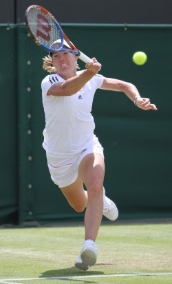 Justine Henin returns the ball on the third day of Wimbledon.
