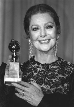 Actress Loretta Young holds up her Golden Globe Award