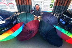 A Chinese man sells umbrellas on a street in Beijing