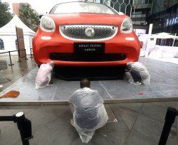 Chinese workers assemble a large MINI automobile display in Beijing