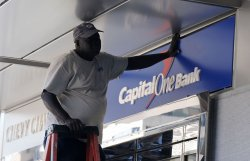 A worker installs a Capital One Bank sign in Washington