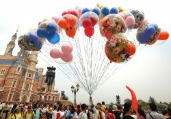 A Chinese Disney employee sells balloons in Shanghai Disneyland Resort, China