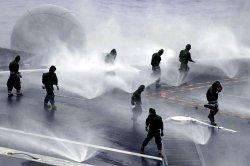Flight Deck personnel on the USS Nimitz conduct a salt-water counter-measure wash-down test