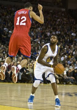 Warriors Dorell Wright waits for 76ers Evan Turner to land before taking a shot in Oakland, California
