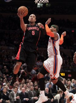Toronto Raptors Jerryd Bayless leaps by New York Knicks Carmelo at Madison Square Garden in New York
