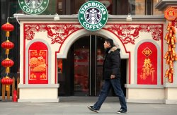 A Chinese man walks past a Starbucks store adorned with traditional Chinese decorations in Beijing