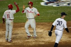 Philadelphia Phillies Shane Victorino slaps hands with Jimmy Rollins after they both come across the plate while New York Yankees relief pitcher David Robertson walks back to the mound in the eighth inning in game 1 of the World Series at Yankee Stadium i