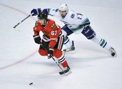 Blackhawks Frolik skates puck as Canucks Hamhuis defends in Chicago