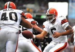 Browns' quarterback Seneca Wallace hands off to Peyton Hills in Baltimore
