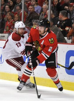 Phoenix Coyotes forward Ray Whitney (13) and Chicago Blackhawks defenseman Duncan Keith (2) go for the puck in Chicago