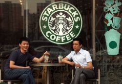 Chinese men drink coffee outside a Starbucks Coffee cafe in Beijing