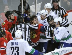 Blackhawks Frolik and Canucks Hansen separated by referees in Chicago