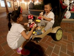 Two Chinese kids play with their Disney dolls in Shanghai Disneyland, China