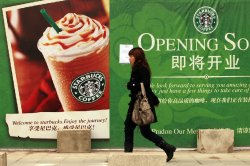 A Chinese woman walks past a Starbucks in Beijing