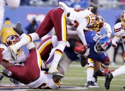 Washington Redskins Kevin Barnes leaps to tackle New York Giants Hakeem Nicks at MetLife Stadium in New Jersey