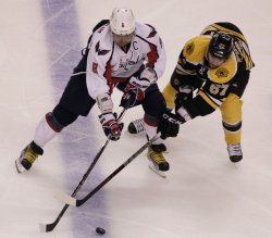 Bruins Pouliot and Capitals Ovechkin battle for puck in second period at TD Garden in Boston, MA.