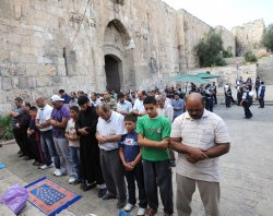 Palestinians pray outside the walls of the Old City of Jerusalem