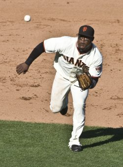 Giants Juan Uribe charges a chopper against the Phillies in game three of the NLCS in San Francisco