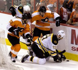 Boston Chara goes to his knees to cover the puck during the third period in Philadelphia.