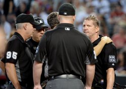 Umpire Kellogg is checked out after being hit by a bat