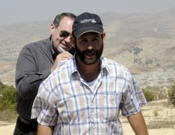 Former U.S. Presidential candidate Mike Huckabee signs an autograph for an Israeli settler in the West Bank