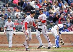 New York Mets Josh Thole picks up the baseball as Washington Nationals Ian Desmond scores a run at Citi Field in New York