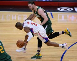Clippers' guard Chris Paul (L) is fouled by Jazz guard Brendan Hayward in Los Angeles