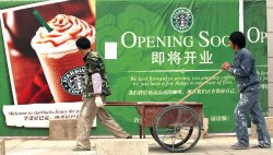 Chinese workers walk past a Starbucks in Beijing