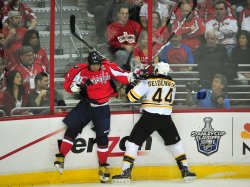 Capitals Alex Ovechkin hits the boards as he fights for the puck against Bruins Dennis Seidenberg in Washington