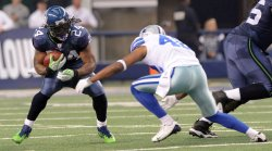 Seahawks Marshawn Lynch rushes as Cowboys Terence Newman closes in at Cowboys Stadium in Arlington, Texas