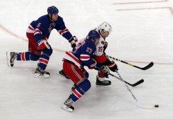 New York Rangers Dan Girardi and Ryan McDonagh battle for the puck with Ottawa Senators Jason Spezza at Madison Square Garden in New York