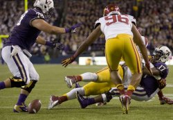 Washington Huskies' quarterback Keith Price (17) fumbles the ball onthe three-yard line after being tackled by USC Trojans Jawanza Starling in Seattle.